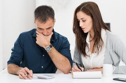 Portrait Of A Worried Couple Calculating Financial Budget