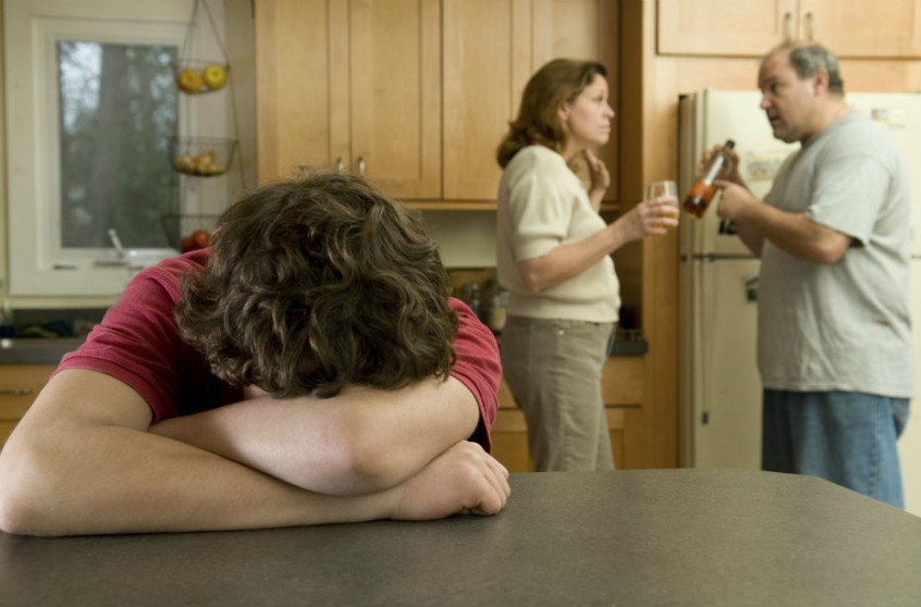 Teen boy putting his head down while his parents yell and fight behind him in the kitchen.