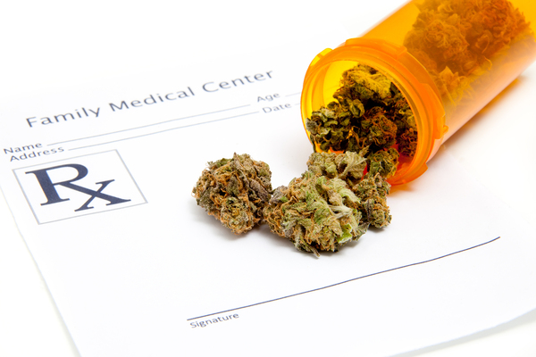 Marijuana coming out of a pill bottle on top of a prescription pad