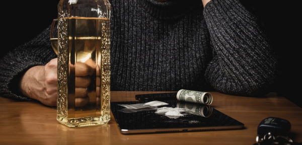 Man with substance abuse places cocaine and alcohol on the table