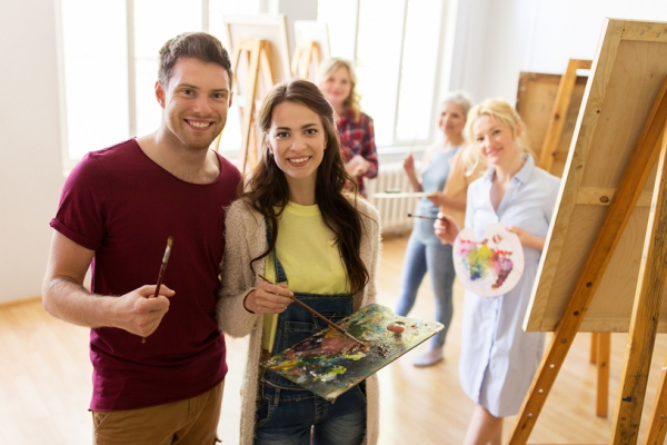 Woman and man getting ready to paint on a canvas