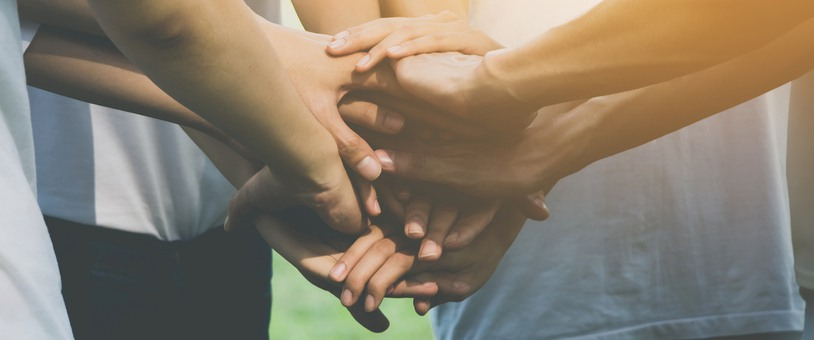 Group of people putting their hands together as a team.