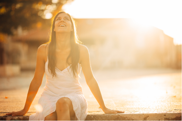 Woman sitting outside looking up at the sun and smiling.