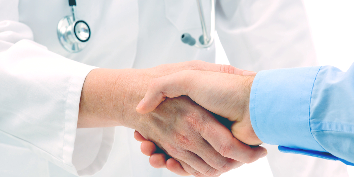 A doctor and a Blue Cross Blue Shield representative discuss insurance for rehab