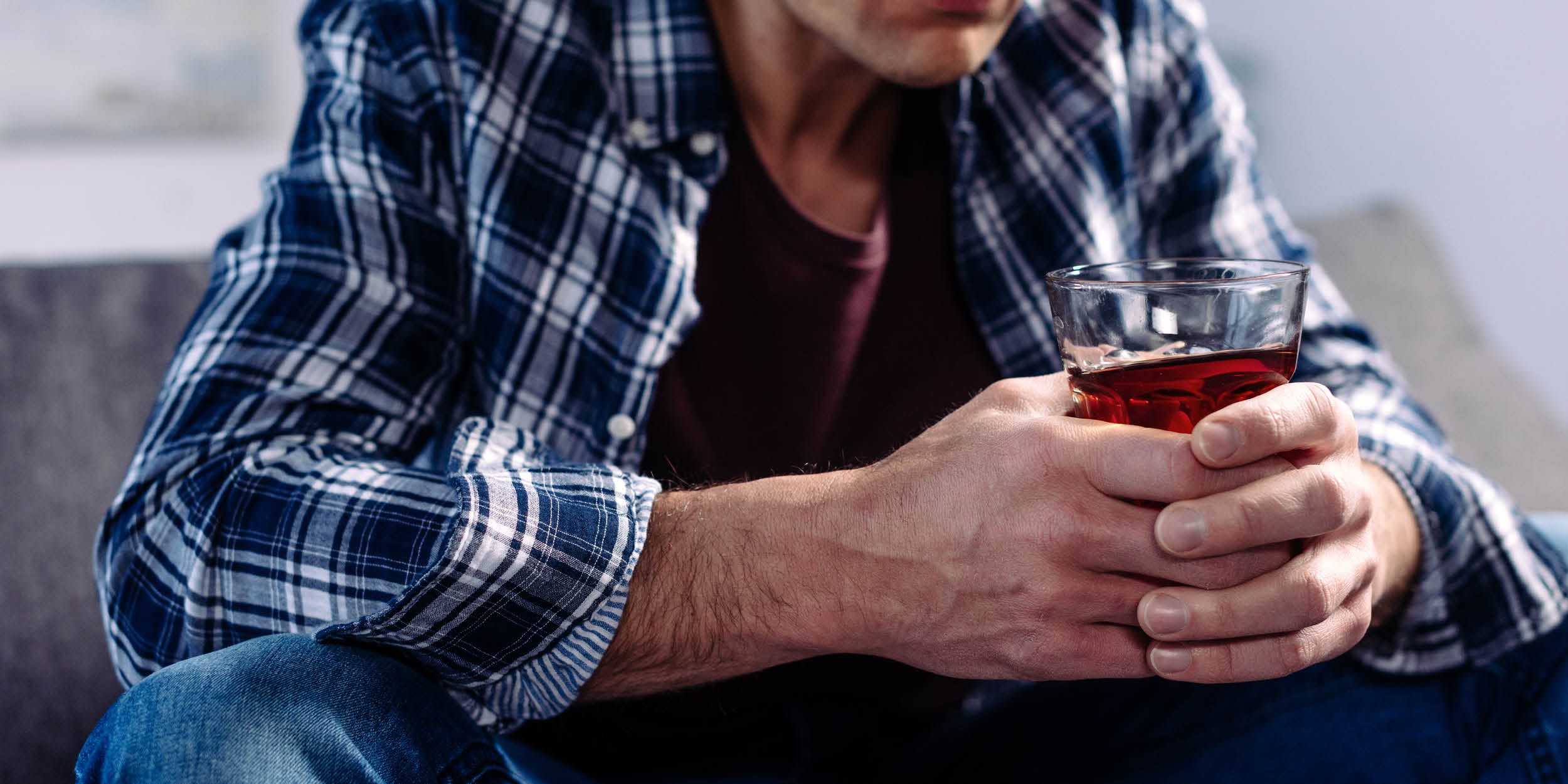 Man holding a cup of liquor at risk of developing alcohol induced psychosis