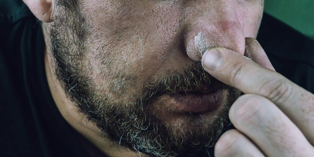 Man wiping cocaine residue off his nose.
